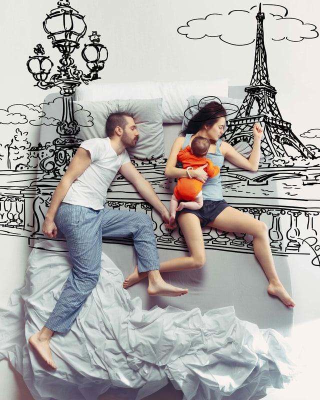 Ein Mann und seine Frau und ihr kleines Kind schlafen im Bett.