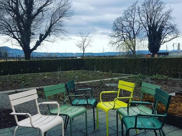 Gartenstühle auf einer Teasse, der Himmel ist Grau, der Boden nass.