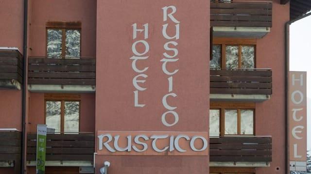 Die Fassade des Hotel Rustico in Laax: Ein rosa Haus mit diversen Fenstern und Balkonen.