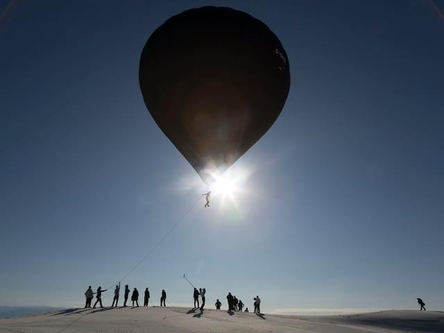 Ein Mann, mithilfe eines riesen Ballons schwebt.