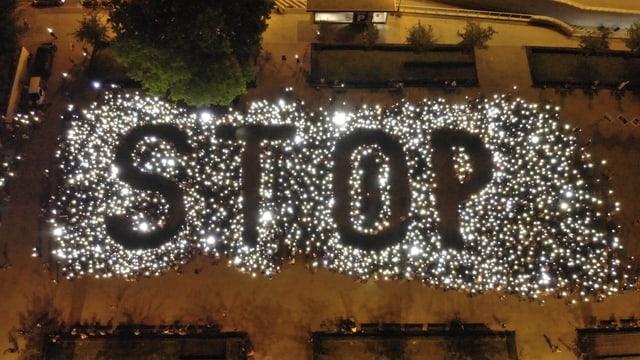 Demonstranten bilden einen Stop-Schriftzug mit Lichtern