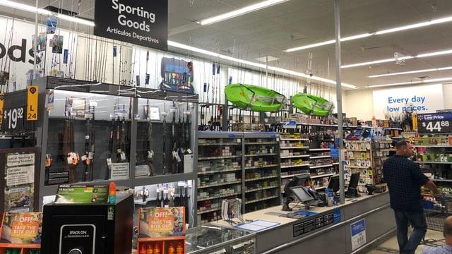 Sportabteilung in einem Supermarkt. Man sieht die oben erwähnten Gegenstände. Eine Vitrine mit Gewehren. Ein Mann mit Einkaufswagen läuft daran vorbei.