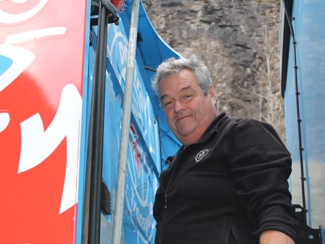 Ein Mann steht hinter der Fahrerkabine des Sattelschleppers.