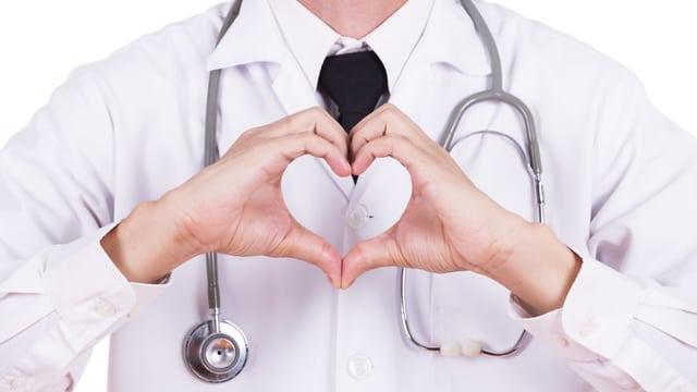 Ein Mann im Arztkittel formt mit seinen Händen ein Herz.