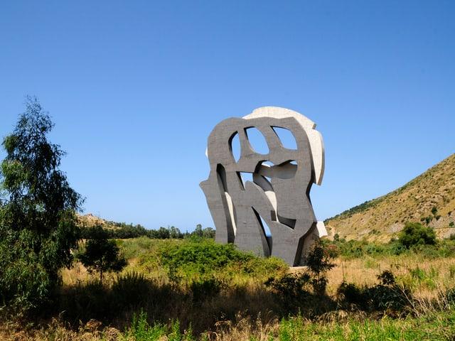 Eine Skulptur in einer Graslandschaft, bestehend aus zwei unterschiedlich gefärbten Stein-Formen.