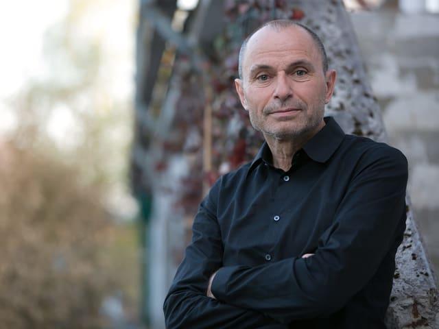 Mann (Norbert Gstrein) mit schwarzem Hemd und fast Glatze steht mit verschränkten Händen vor einem Baum.