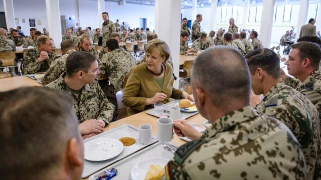 Die deutsche Bundeskanzlerin Angela Merkel isst mit Soldaten in Afghanistan.