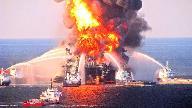 Eine brennende Bohrinsel ist von Löschschiffen umgeben.