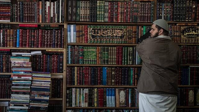 Ein Moslem steht vor einem Gestell voller islamischer Bücher.