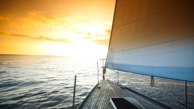 Ein Segelschiff segelt dem Sonnenuntergang entgegen.