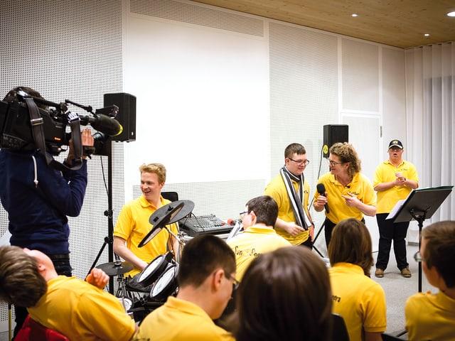 Kameramann steht im Proberaum mit den behinderten Sängerinnen und Sänger und filmt.