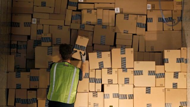 Ein Mitarbeiter eines Verteilzentrums von Amazon in Phoenix im US-Bundesstaat Arizona stapelt Pakete.