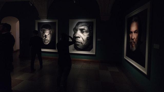 Bilder hängen an Wand. Dunkler Raum.