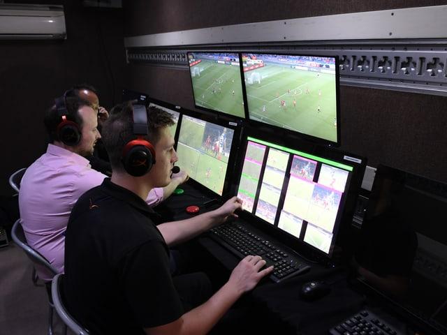 Drei Video-Assistenten in einem Raum mit mehreren Bildschirmen