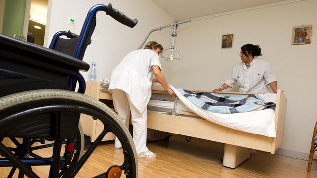 Zwei Pflegerinnen machen ein Bett. Im Vordergrund steht ein Rollstuhl.