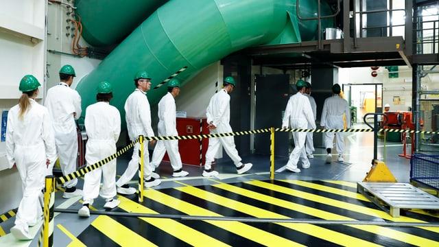 Eine Besuchergruppe geht in Schutzanzuegen durch das Kernkraftwerk Mühleberg, am 29. August 2018 in Muehleberg.