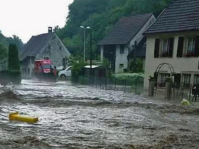 Überflutete Strasse in einem Dorf im Jura.