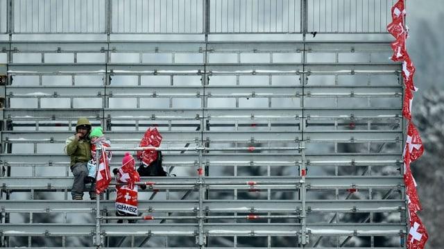 Drei Zuschauer mit Schweizer Fahnen auf einer sonst leeren Tribüne.
