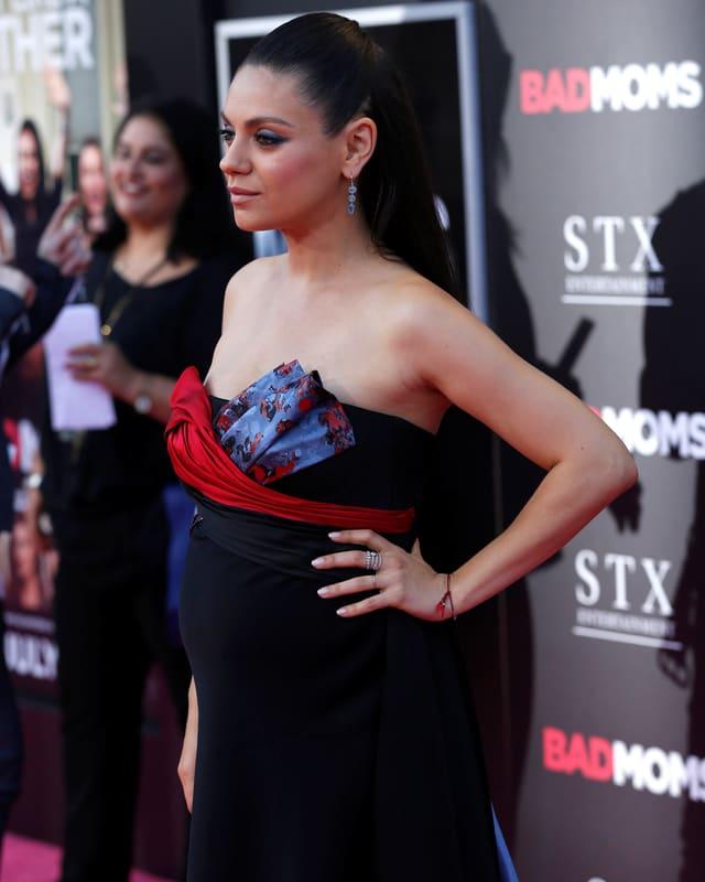 Mila Kunis in einem schwarzen Kleid auf dem red Carpet. Der Babybauch ist deutlich zu erkennen.