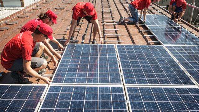 Ein paar Männer montieren Solarzellen auf einem Dach.