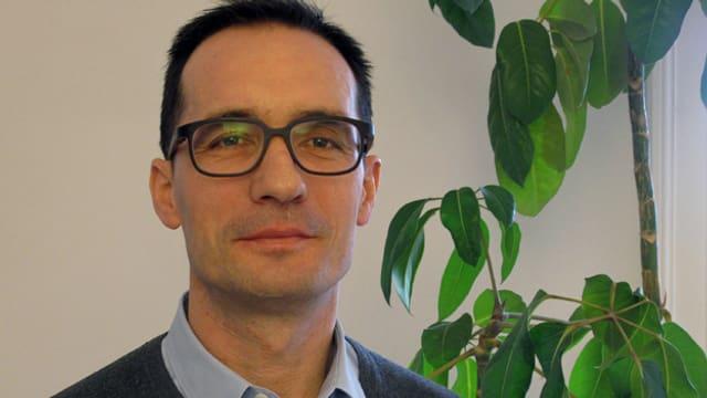 Ein Mann mit Brille vor einer grünen Pflanze.