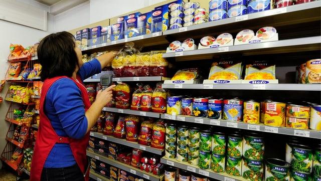 Mitarbeiterin eines Detaillisten vor einer Auslage mit Lebensmitteln