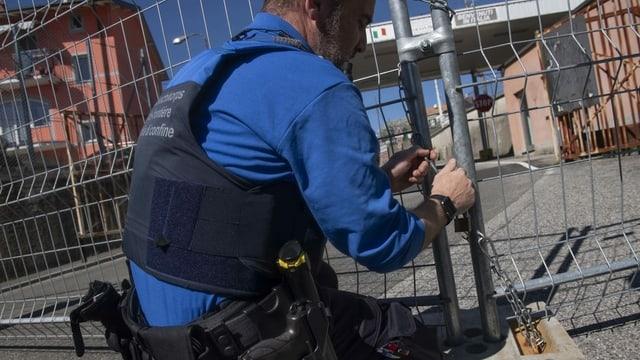 Ein Grenzwächter schliesst am 11. März den Grenzuebergang San Pietro di Stabio zwischen der Schweiz und Italien mit Gittern und Ketten.