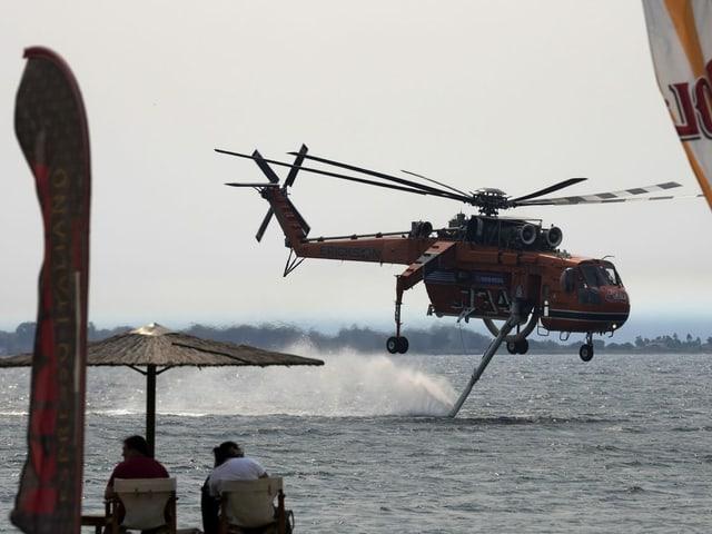Un elicottero riempie l'acqua vicino alla spiaggia.