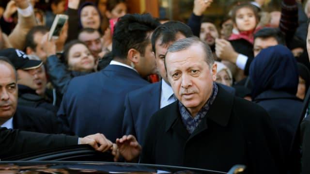 Erdogan steigt inmitten einer Menschenmenge in ein Auto ein.