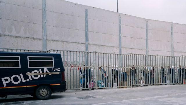 Eine Mauer, vor der ein Polizeiauto steht und Menschen mit Tüten