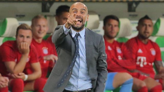 Bayern-Trainer Pep Guardiola steht an der Seitenlinie und erteilt mit erhobenem Zeigefinger Anweisungen. Im Hintergrund sitzen die Ersatzspieler auf der Bank.
