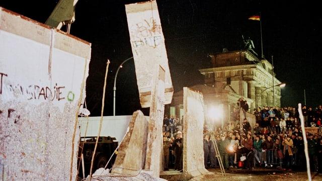 Der Abriss der Berliner Mauer beim Brandenburger Tor mit Baggern und vielen Zuschauern.