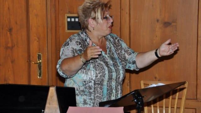 Die blondhaarige Frau mit Brille zeigt mit hochgehaltenen Armen eine typische Dirigenten-Pose.