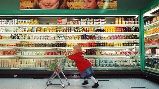 Ein Kind schiebt einen Einkaufswagen an einem Coop-Regal vorbei