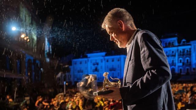 Ein Mann mit einer goldenen Leopardenstatue geht im Regen eine Treppe hinunter.
