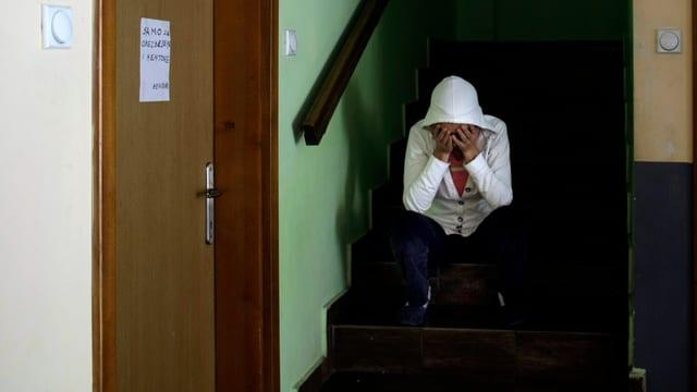 Eine Person kauert auf einer Treppe.
