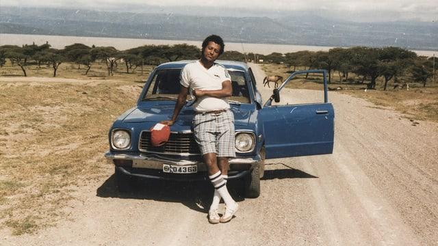 Ein junger schwarzer Mann in weissen Tennissocken vor einem blauen Auto.