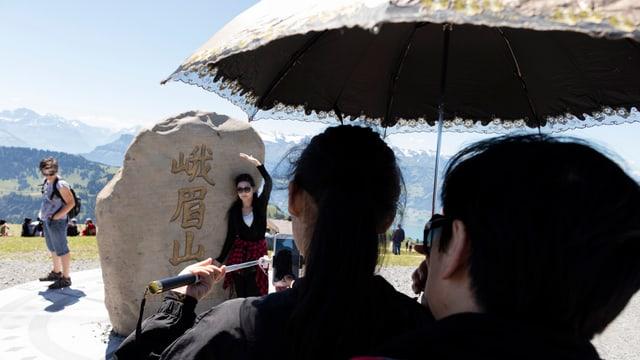 Chinesische Touristen fotografieren auf der Rigi den Felsbrocken, der vom chinesischen Berg Emei Sha stammt.
