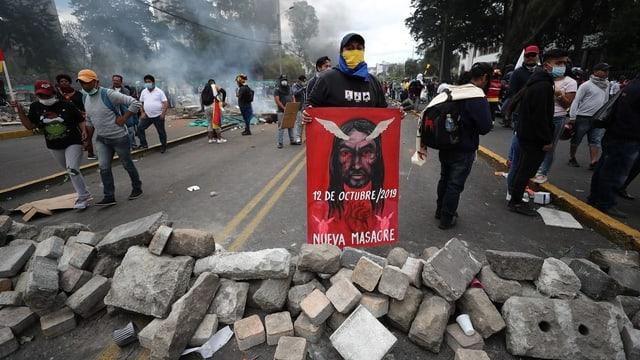 Demonstrant hinter Steinbarrikade mit Protestschild