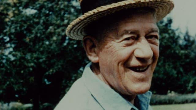 Ein lächelnder alter Mann ist draussen mit Hut.
