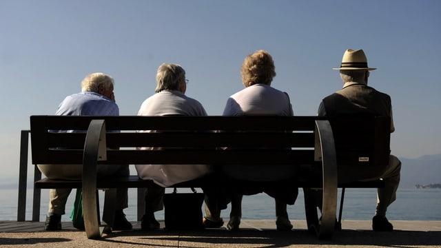 Quatter persunas pensiunadas sesan sin in banc e miran vers in lai.