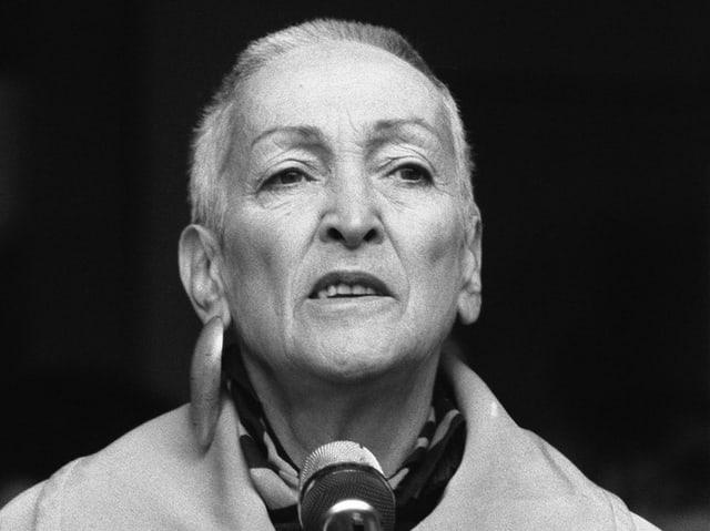 Schwarz-Weiss-Foto von Meret Oppenheim mit kurzem Haar und einem grossen, metallenen Ohrring.