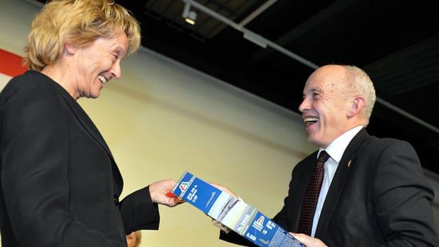Eveline Widmer-Schlumpf überreicht Kollege Ueli Maurer ein Geschenk.