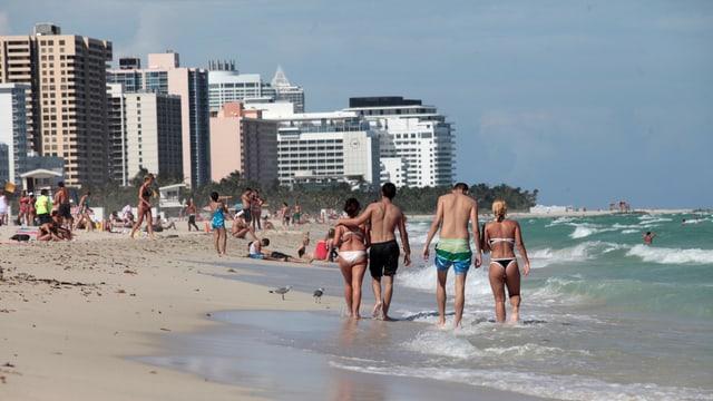 Menschen laufen in Badekleidern am Strand von Miami Beach, im Hintergrund Hochhäuser.