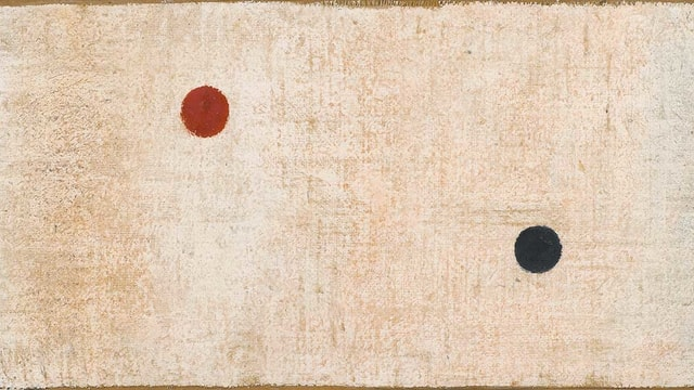 Ein roter und ein schwarzer Punkt auf weissem Gund.