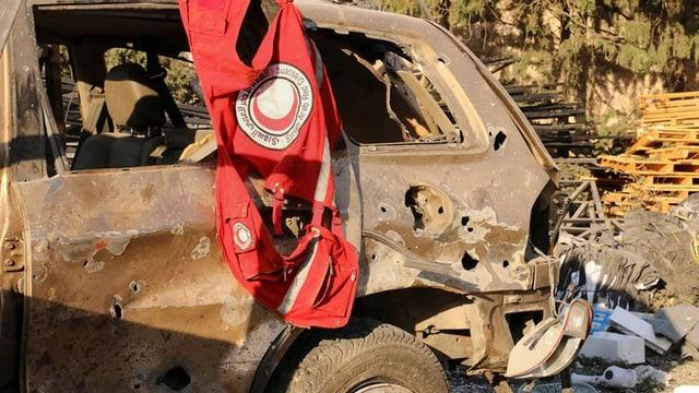Ein zerstörtes Auto, über dessen Tür eine Weste des Roten Halbmondes hängt.