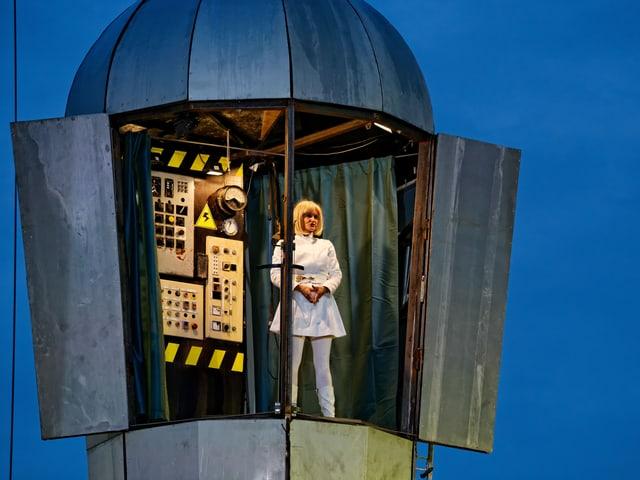 weissgekleidete Frau auf einem Turm mit Schaltzentrale