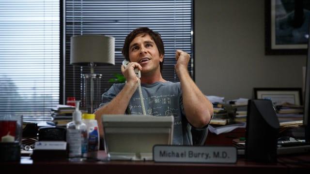Schauspieler Christian Bale hinter einem Schreibtisch am Telefon.