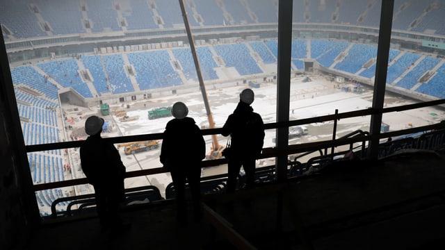 Arbeiter blicken auf leere Ränge eines Fussballstadions.