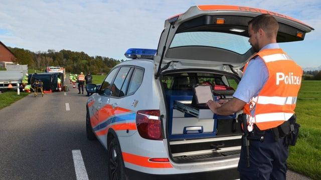 Polizist nimmt am Computer im Auto die Daten auf.